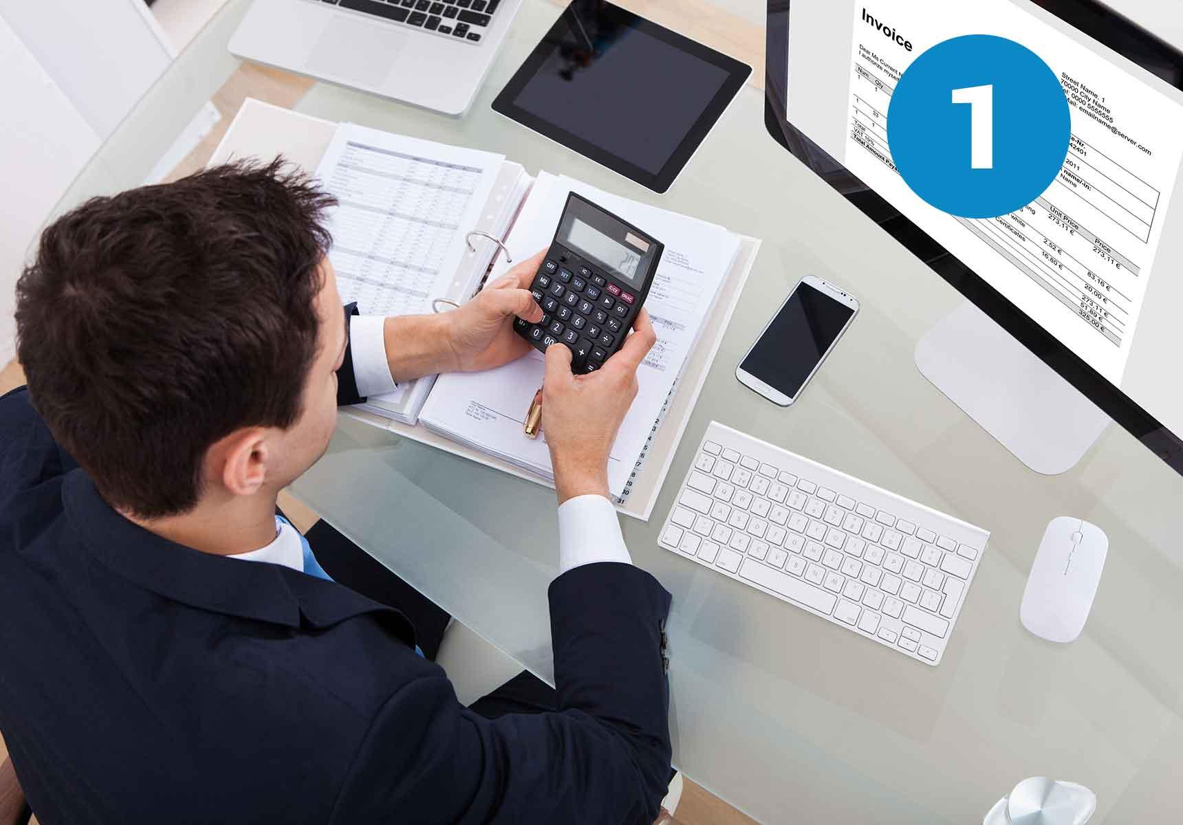 Mann sitzend mit Taschenrechner und Vertrag vor Computer